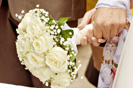 Young couple of lovers who are just married with bouquet photo