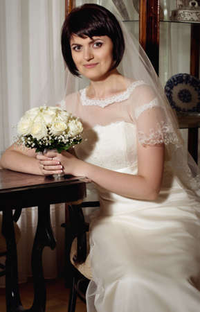 Beautiful bride with bouquet of flowers in white dress photo