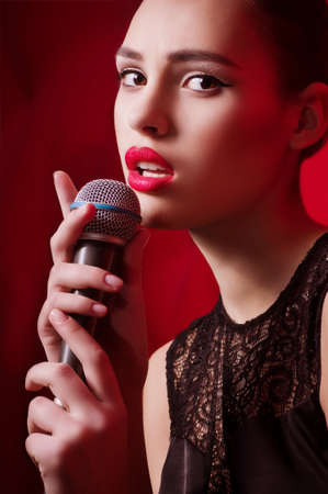 Beautiful young woman singer with microphone photo