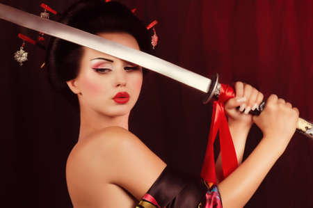 samoerai: Mooie geisha in kimono met samurai zwaard Stockfoto