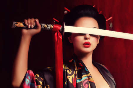 Beautiful geisha in kimono with samurai sword Banco de Imagens - 25613087