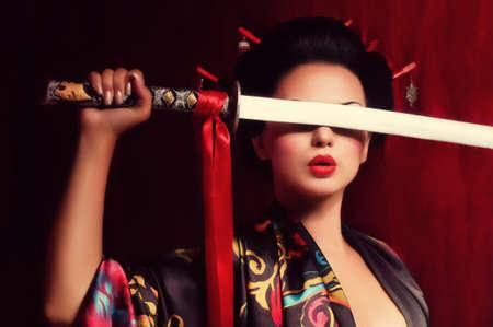 Belle geisha en kimono avec l'épée de samouraï Banque d'images