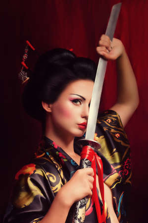 katana: Mooie geisha in kimono met een samurai zwaard