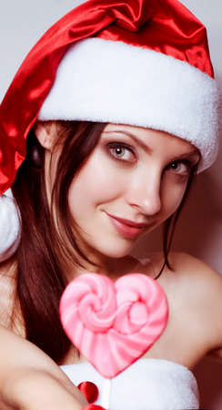 Beautiful young girl in Santa Claus clothes with pink spiral lollipop on white background  photo