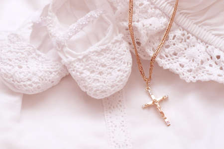 Baby shoes and white dress with golden cross for Christening photo
