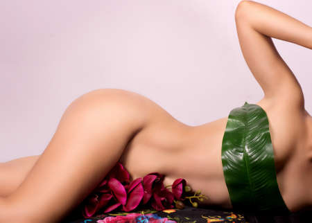 Close up of a woman beautiful body with flower on her pubes photo