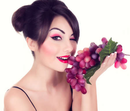 Beautiful young woman with red grape on white background photo