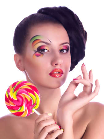 Beautiful young girl with pink spiral lollipops on white background  photo