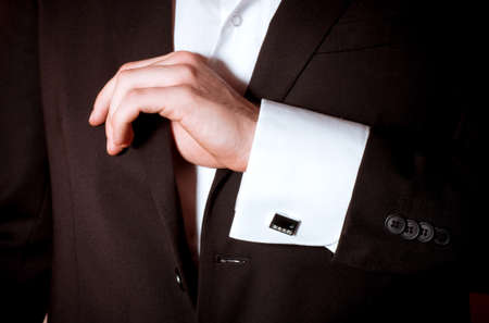 cuff link: Closeup of a man in black suit correcting a sleeve