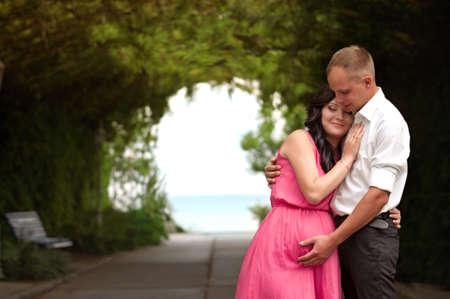 Beautiful pregnant woman in green garden photo