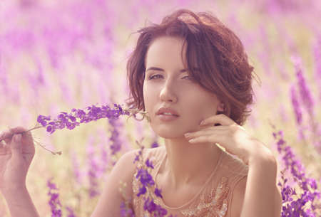 Beautiful woman in spring garden with violet flowers Stock Photo - 30548496