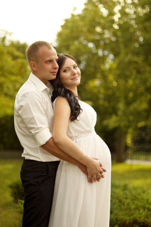 Beautiful pregnant woman with a man in green garden photo