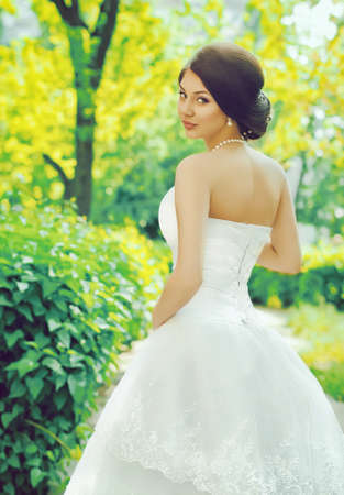Beautiful bride with stylish make-up in white dress in spring garden photo