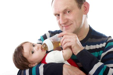 feeds: Happy grandchild feeds grandfather Stock Photo
