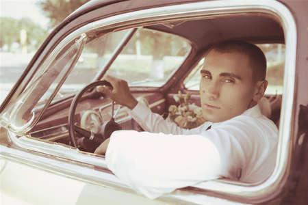 Young groom inside a classic retro car photo