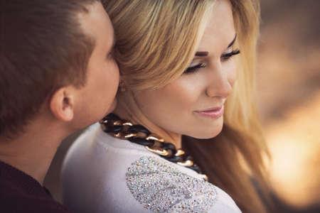 baiser amoureux: jeune couple portant sur la pelouse du parc  Banque d'images