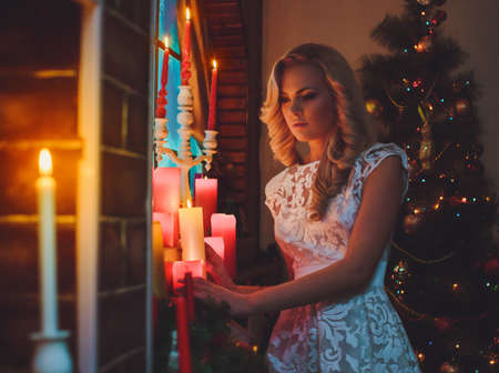 miracle tree: Young woman near a new-year tree with gifts and candles