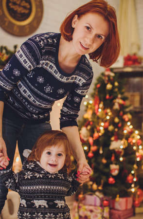 baby near christmas tree: Beautiful mother with baby girl near a Christmas tree