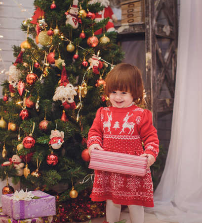 baby near christmas tree: Beautiful baby girl near a Christmas tree with gifts