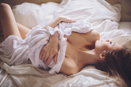 nude blond girl: Beautiful young woman in white bathrobe in bedroom at home Stock Photo