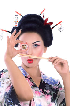 japanese kimono: Young woman in Japanese kimono with chopsticks and sushi roll, isolated on white background.
