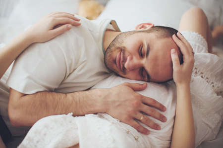 Beautiful pregnant woman and her husband is in their bedroom