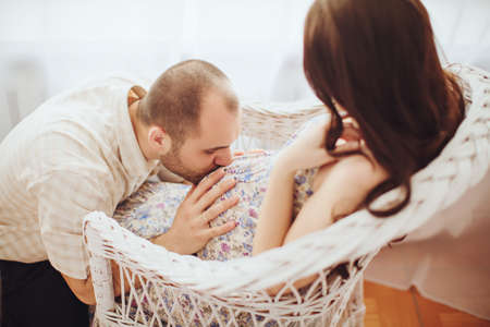 pregnant woman with husband: Beautiful pregnant woman and her husband is in their bedroom