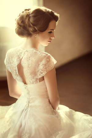 wedding hairstyle: Beautiful bride with stylish make-up in white dress