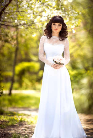 happy wedding: Beautiful bride with stylish make-up in white dress in spring garden