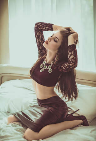 Portrait of beautiful young woman with makeup in fashion clothes in black dress on bed