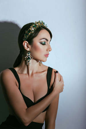 Beautiful girl model with professional makeup, in jewelry. Golden crown in style DG photo