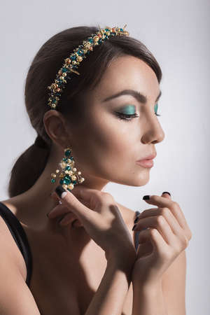 Beautiful woman model with professional makeup, in jewelry. Golden crown photo