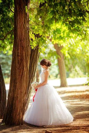Mooie bruid in witte jurk in de tuin