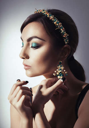 Beautiful woman model with professional makeup, in jewelry. Golden crown in style D&G photo