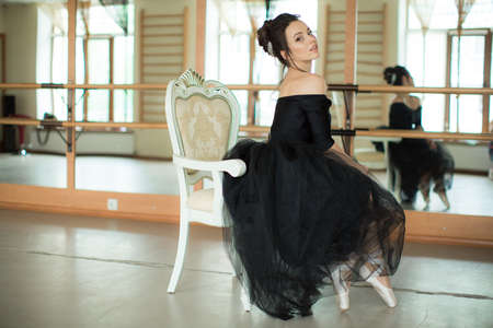 prime adult: young ballerina is relaxing in class room