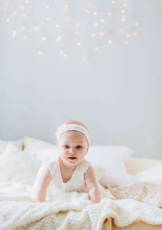 bed sheet: Portrait of a beautiful little girl on the bed