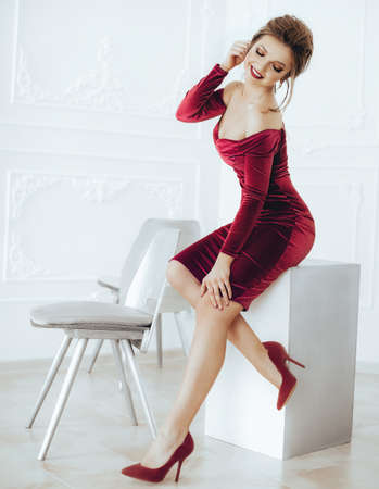 Portrait of a beautiful young woman with makeup in red dress