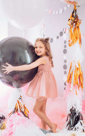 Beautiful little girl celebrating birthday party with big bouncy balls. Family celebration of the child