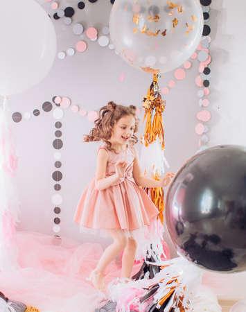 Mooie meisje het vieren verjaardagspartij met grote bouncyballen. Familiefeest van het kind