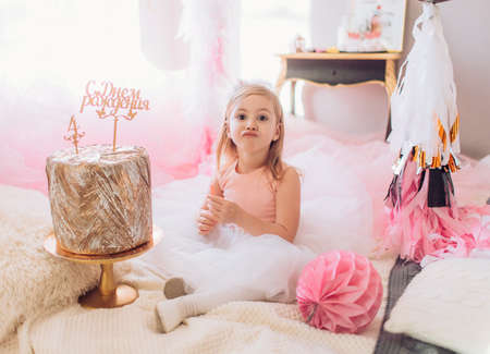Beautiful little blonde girl celebrating birthday party with big bouncy balls. Family celebration of the child