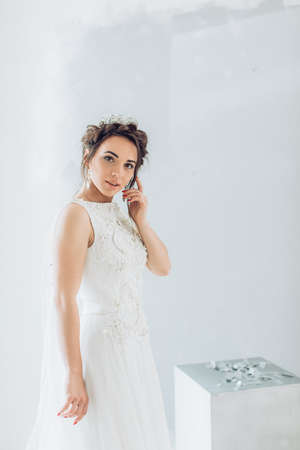 Portrait of beautiful young woman with makeup in white wedding clothes