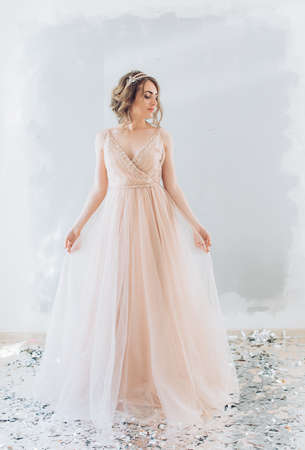 Portrait of beautiful young woman with makeup in pink wedding clothes