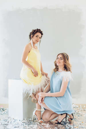 Portrait of beautiful young women with makeup in yellow and blue fashion clothes Banque d'images