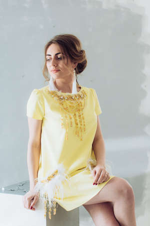 Portrait of beautiful young woman with makeup in yellow fashion clothes