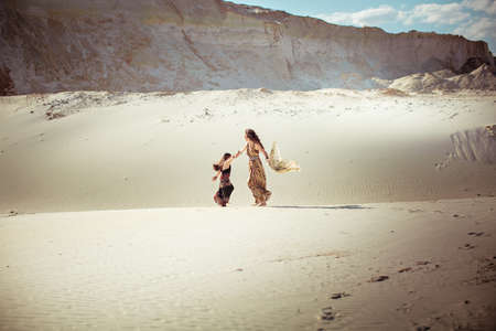 Beautiful young woman in dress on sand quarry and kid sister Banque d'images