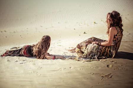 Mooie jonge vrouw in jurk op zandgroeve en kind zus