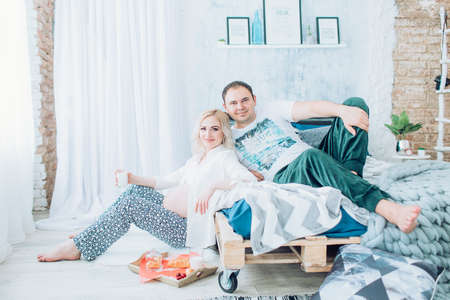Beautiful pregnant woman with her husband in her bedroom Banque d'images - 108338979
