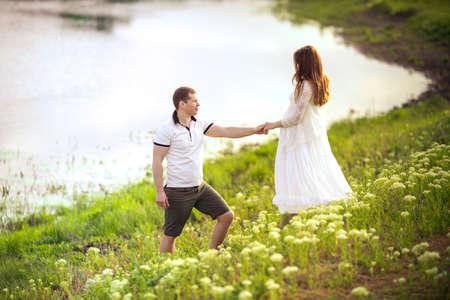 Mooie zwangere vrouw met haar echtgenoot in een groene tuin