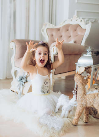 Beautiful little girl in white dress with christmas tree decoration