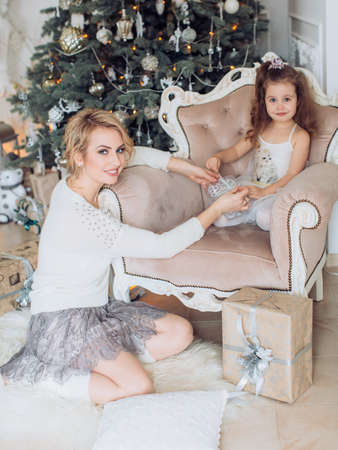Baby girl in white dress and mother near Christmas tree